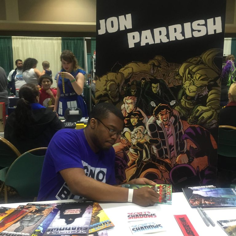 Jon Parrish, writer and creator of SECRETS AND SHADOWS and CLUSTERF#%K, mans his table at St. Louis Comicon (picture from shadowsandsecrets.net)